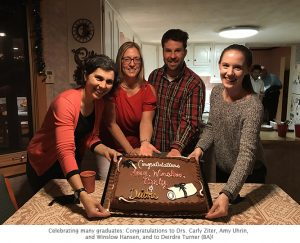 Photo of all 4 grads with cake